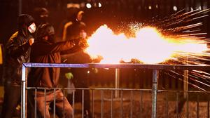 Youths launch fireworks at the PSNI during the protests in Belfast. Photo: Liam McBurney/PA Wire