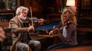 Patrick Bergin teaches fellow actor Rose Reid to play the fiddle