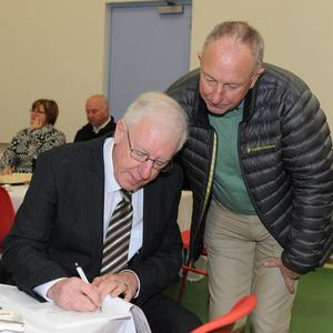 Former Minister Dermot Ahern gets Noel Sharkey to sign a copy of his book 'A Journey Through Time from Land to Sea' at the reception held after the Eucharistic Celebration of Thanksgiving for the refurbishment of St. Oliver Plunkett Church by Archbishop Eamon Martin