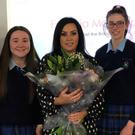 Gillian Moore Brady is presented with a bouquet of flowers by pupils from Bush PP