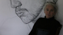 Artist Leanne Mullen in front of one her portraits which are currently displayed in shop windows in Clanbrassil Street