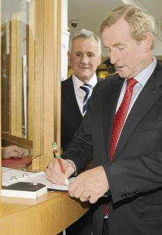 Taoiseach Enda Kenny signs the visitors' book at Government buildings on St Alphonsus Road.