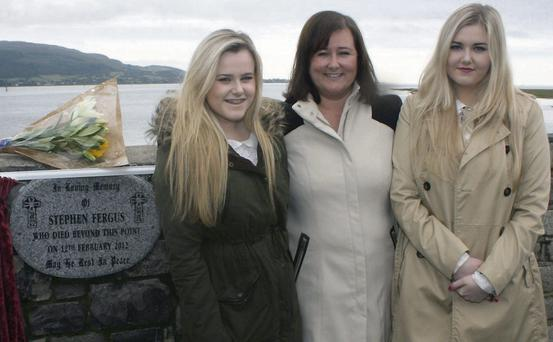 Amy, Lisa and Erin Fergus unveil a memorial to their late husband and father at Soldier's Point on Saturday.