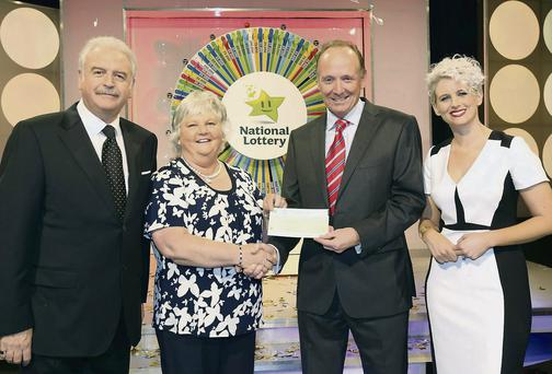 Marty Whelan, game show co-host; Leontia Toal, €40,000 winner; and Declan Harrington, Head of Finance, The National Lottery.