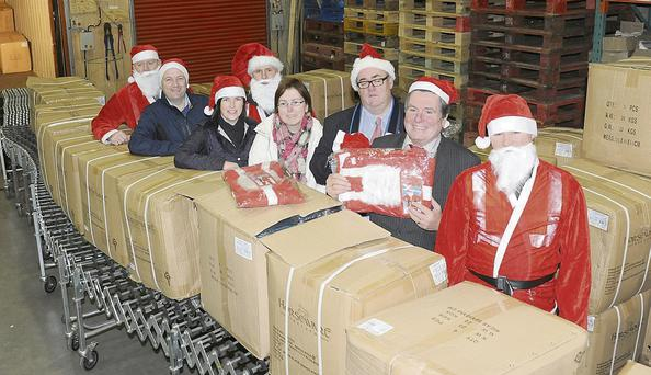 Paddy Matthews and Jimmy Cumiskey, Dundalk Chamber of Commerce, with David Minto of Horseware, along with Maeve Yore, SNAP and Paula Hanlon, Lordship Children's Respite Centre and some of the Santas who are taking part in the Dundalk Santa Fun Run in Horseware for the arrivial of 4,000 Santa suits for the Run.