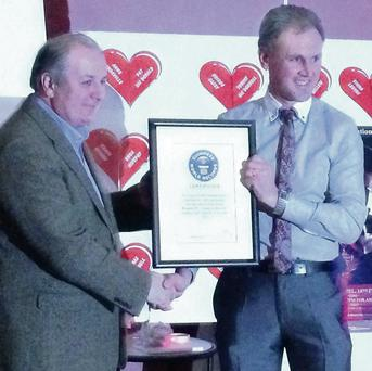 Gavin Duffy presents Roche Emmets Chairman, Simon Allen, with their official Guinness World Record.
