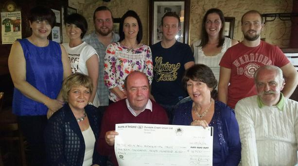 Fionnuala and Paddy Dullaghan (right) presenting the cheque for €16,700 to Colin and Eithne Bell. Also pictured are members of both families.