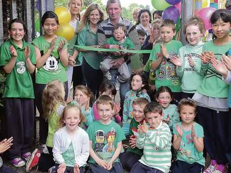 Shane Keenan together with Peadar Keenan, principal Regina O'Malley, Clare O'Hagan of Omeath Tidy Towns and pupils from Scoil Naomh Bríd, Ardaghy.