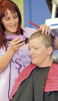 Carmel Corbett gets her head shaved by Sinead O'Connor in aid of the Cara Cancer Care Centre. Photo: Ken Finegan