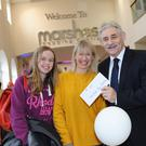 Centre Manager Harry Traynor presents Sarah Mac Ruairí, Blackrock, with her prize of €1,000, watched by her daughter Beibhinn
