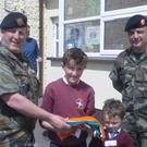 Members of the 27th Infantry Battalion present a tricolour to Kilcurry NS pupils after their original 1916 presentation flag was stolen
