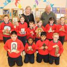 Fr. Declan O'Loughlin, teacher Muirne Lawlor and pupils at the 'Praying your Beads' exhibition in St. Joseph's National School