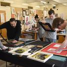 Students from the Graphic Design class prepare some of their work for the annual Ó Fiaich Institute of Further Education art exhibition which will be held in the Marshes Shopping Centre. Picture: Ken Finegan
