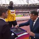 Usain Bolt receives his bronze medal from Sebastian Coe, with medal being borne by Ronnie Murray