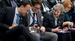 Irish Prime Minister Leo Varadkar, left, shows his decorative socks to British Prime Minister Theresa May, second right, during a round table meeting at an EU summit in Goteborg, Sweden.
