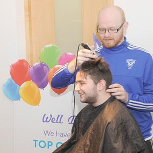 Staff members watch Callum Flanagan getting his head shaved by Terry O'Reilly during the mad hair charity day in The Irish Life Centre