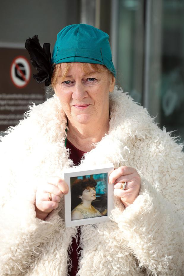 Anne Delcassian with a framed photograph of her sister Irene outside the Central Criminal Court last week. Pic: Collins Courts