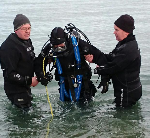 Members of Dundalk Sub Aqua Search and Recovery help a new recruit with their diving gear