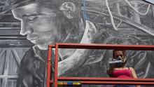 Artist Chule working on her mural on Park Street during the summer