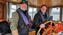 TV chef Neven Maguire at the helm of 1945 Dutch Tug 'Brienne' with owner Shane Reenan