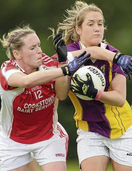 Marie O'Connell gets in close to tackle Wexford's Katie Redmond.