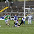 Goalkeeper Vincent Egan gets an arm to Conor Martin's shot