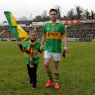 Kayden Fisher flies the flag for Sean O'Mahony's as he leaves the field with Dad Stephen