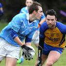 Stephen Moonan of Newtown Blues looks to pass to a teammate as Kilkerley's Seamus Fagan closes in