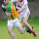 St Bride's Padraic Mackin keeps pace with the Clans' Mark McGeown