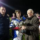 Captain Ross Nally receives the trophy from Mark Gilsenan and John Lennon
