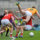 Antrim's Martin Johnson takes a tumble over James Stewart as Jim McEneaney offers support
