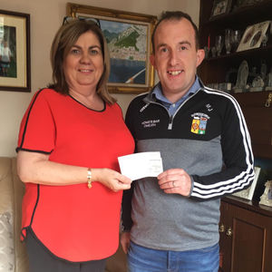 Mary Bellew receives her cheque for €20,000 from club member Mattie Jones after winning the Cuchulainn Gaels lotto jackpot last week