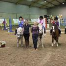 Happy competitors receive their rosettes after the X poles class at Ravensdale Lodge's indoor horse and pony training league on Friday evening. Joshua Murphy who competed at his first ever show on Friday is pictured with his pony Silver Wishes and his Mum Deirdre along with Casey Jane Creegan and Gypsy, Amy Robinson and Basil and Eoin McEnaney and Harriett