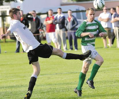 Owen Armstrong gets on the scoresheet for Shamrocks FC despite close attention from Anto Reilly.