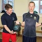 Robbie Farrell showing a novice 'dumbbell' how to lift weights