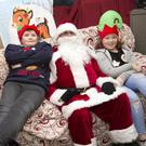 Matthew McNulty, Alex Nolan and Gracie Keogh with Santa in his grotto at the Hillview Christmas Craft Fair