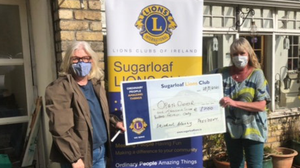 Niamh O'Mahony, Sugarloaf Lions, presenting a cheque for €1,700 to Suzanne Cox, Development Officer with Open Door
