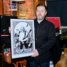 Artist Conall McCabe with a print of an original piece that he presented to Thin Lizzy's Scott Gorham
