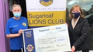 Sonia Walsh of Greystones Cancer Support accepting the cheque from Von McDonald of Sugarloaf Lions Club