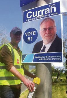 Stephen Donnelly puts up election posters on behalf of Tom Curran.