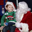 Ceilim Treacy tells Santa how he broke his arm falling off the couch