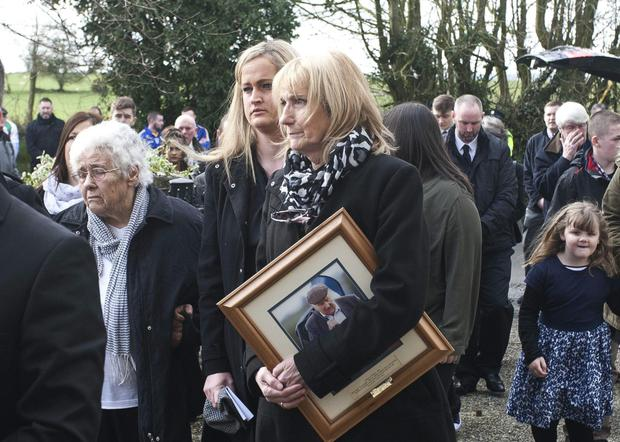 Peter's sister Kathleen, granddaughter Lisa and daughter Josie, clutching a photo of her beloved dad, at St Brigid's Church, Talbotstown