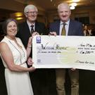 Lady Captain Bernie Jones, Captain Dermot O'Brien, and Gabriel Dooley present the cheque to Evanne Cahill
