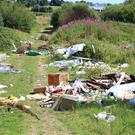 Household waste among tons of waste dumped in the field above the entrance to Charlesland running track last month. It has now been cleaned up