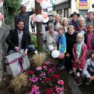 Cllr Stephen Matthews Cathaoirleach of Bray Municipal District cuts the ribbon on the name stone for Albert Walk in Bray watched by members of the Tidy Towns, Edible Bray and Common Ground