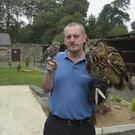 Tom Byran with a little owl and a European eagle owl