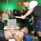 Tony Black hammers down on Alan Connolly as he lies on a bed of nails