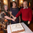 Philipa Bridge, Ann Murdiff and Frank Kelly – the three members who have been with the society the full 30 years – cut the cake
