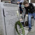 Cian Murray places a single lily on the 1798 monument on Castle Street in memory of Martin McGuinness