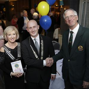 Teresa Dineen, district governor, with new president Karl Ó Broin, who accepts the chain of office from outgoing president Jerry Teehan